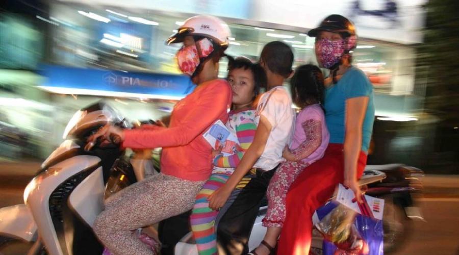 Mobiles Wohnzimmer: Familie in Hanoi auf Moped unterwegs