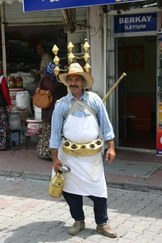 Türkischer Mann mit Messingkessel aus denen er ein heißes Süßholzgetränk verkauft