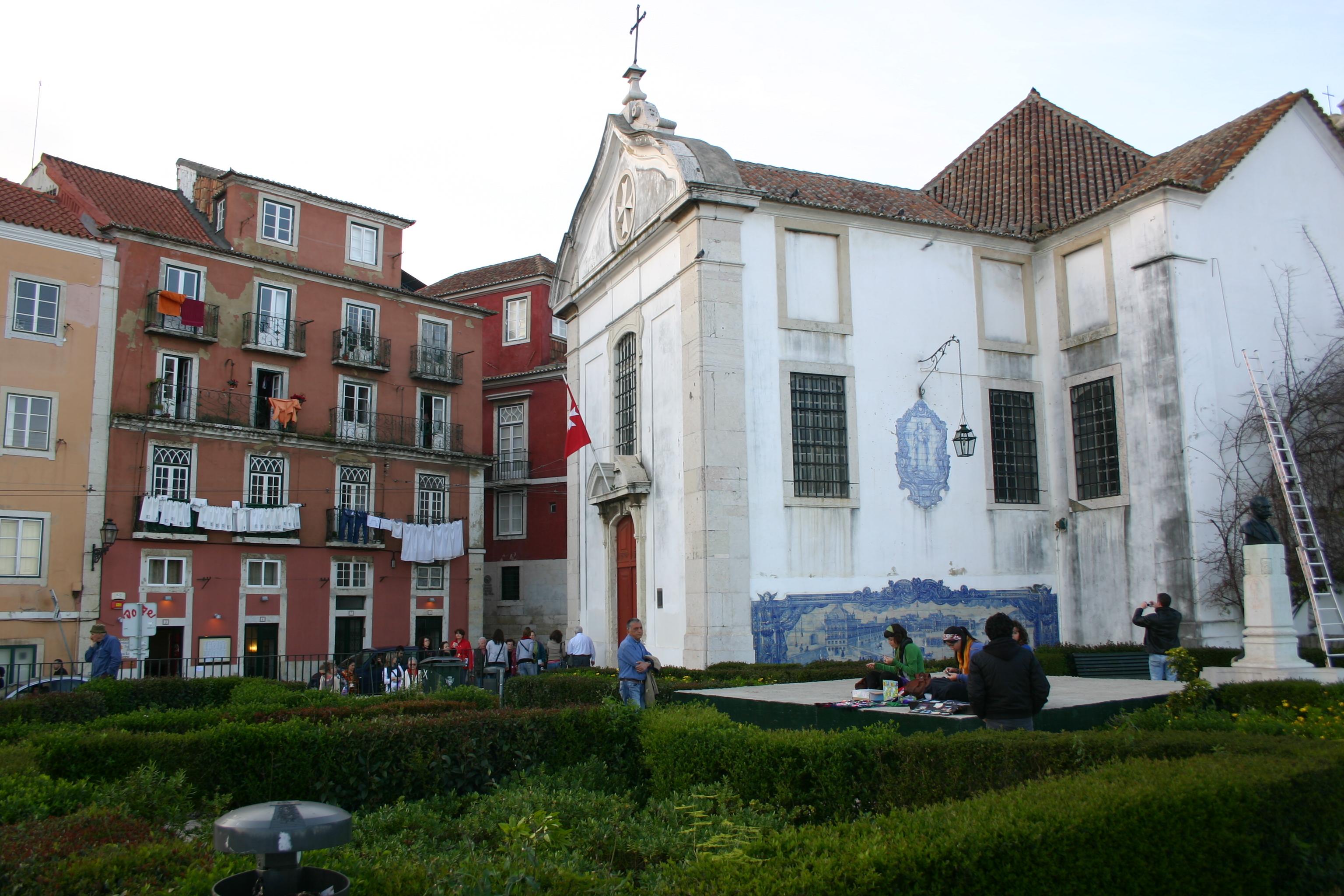 Lissabon in Portugal: Aussichtspunkt Santa Luzia vorbei. Kunsthandwerkerinnen fertigen Souvenirs, bunte Wäsche trocknet an opulent gekachelten Häuserfassaden