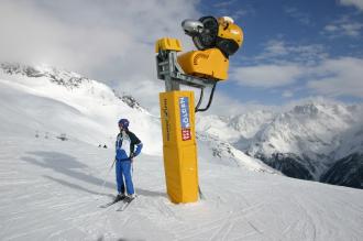 Schneeroboter und Nutznießer: Tourist neben Schneemaschine
