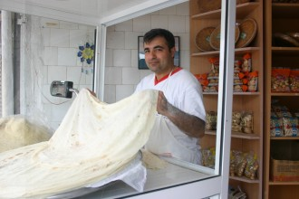 Am Rande der Altstadt unweit des Basars bereitet der Bäcker den Teig für ein riesiges Fladenbrot zu