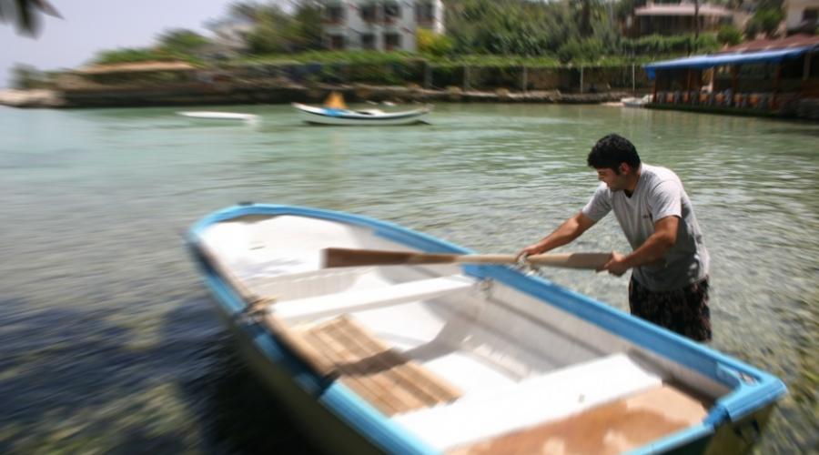 Ein Mann trägt ein Paddel am Boot