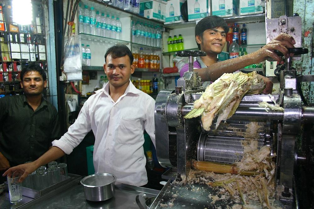 Drei junge Männer an einem Zuckerrohrsaft-Stand am Andheri Bahnhof in Mumbai
