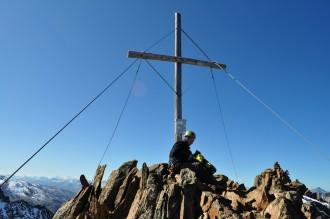 Fabian Stahl am Gipfelkreuz oben auf der Spitze vom Wiesjagglkopf auf 3217 Meter Höhe