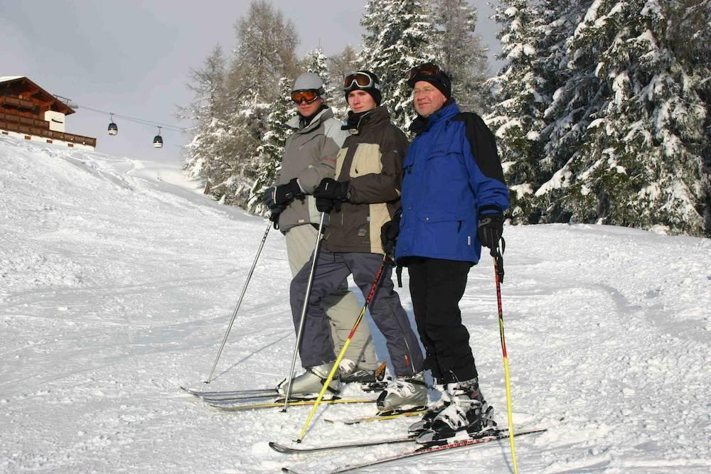 Familie mit Vater und den beiden Söhnen beim Skifahren am Kronplatz