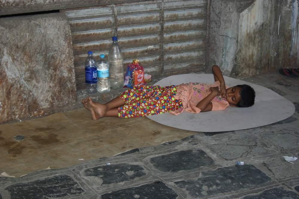 Nach harter Arbeit: Kind schläft in Mumbai (Bombay) auf der Straße im Stadtteil Fort