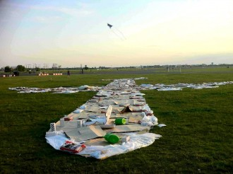 Säcke mit Spielsand beschweren ein Pappe-Flugzeug mit Giekannen