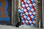 Auf der Ravey Street legt Künstler Carl Cashman Hand an einem Rolltor an.