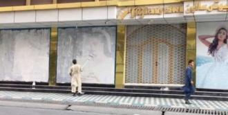 """""""Erasing women from public spaces"""", in Kabul, Afghanistan übertünchen Händler die Werbung an den Fassaden der Läden, die Frauen darstellen."""