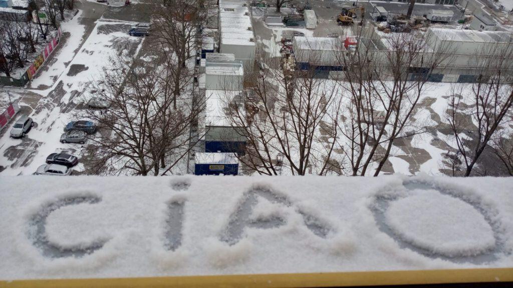 """""""Ciao"""" steht in Schnee geschrieben auf dem Fensterbrett"""