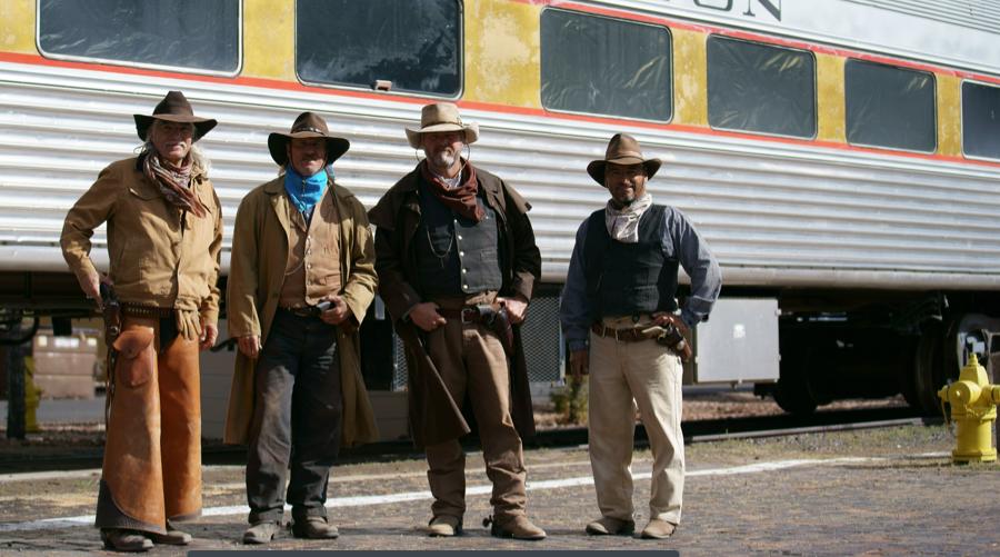 """Von singenden Cowboys und Zugräubern... Ein zusätzliches Highlight und für keinen Wildwest-Liebhaber zu verpassen, ist die Show, die in Williams von der """"Cataract Creek Gang"""" vor der Abfahrt des Grand Canyon Railways präsentiert wird. Dabei bleibt es aber nicht: Auf der Rückfahrt vom Canyon nach Williams, reiten die Cowboys der """"Cataract Creek Gang"""" neben den Waggons her, bevor sie den Zug zum Halten bringt und zusteigen. Danach imitieren die Zugräuber auf unterhaltsame Art und Weise einen Überfall, bevor sie nach einer gewissen Zeit vom Sherriff an Bord verhaftet werden. An der Endstation in Williams posieren sie für gemeinsame Fotos mit den Passagieren."""