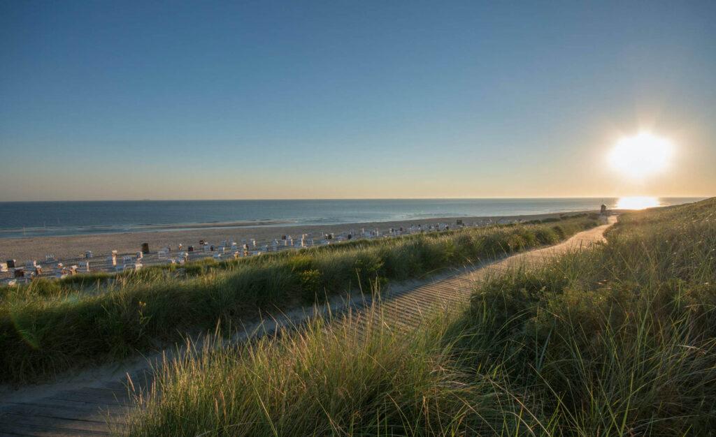 Blick vom Strandzugang: Sonne geht auf am Hauptstrand der der deutschen Nordseeinsel Spiekeroog