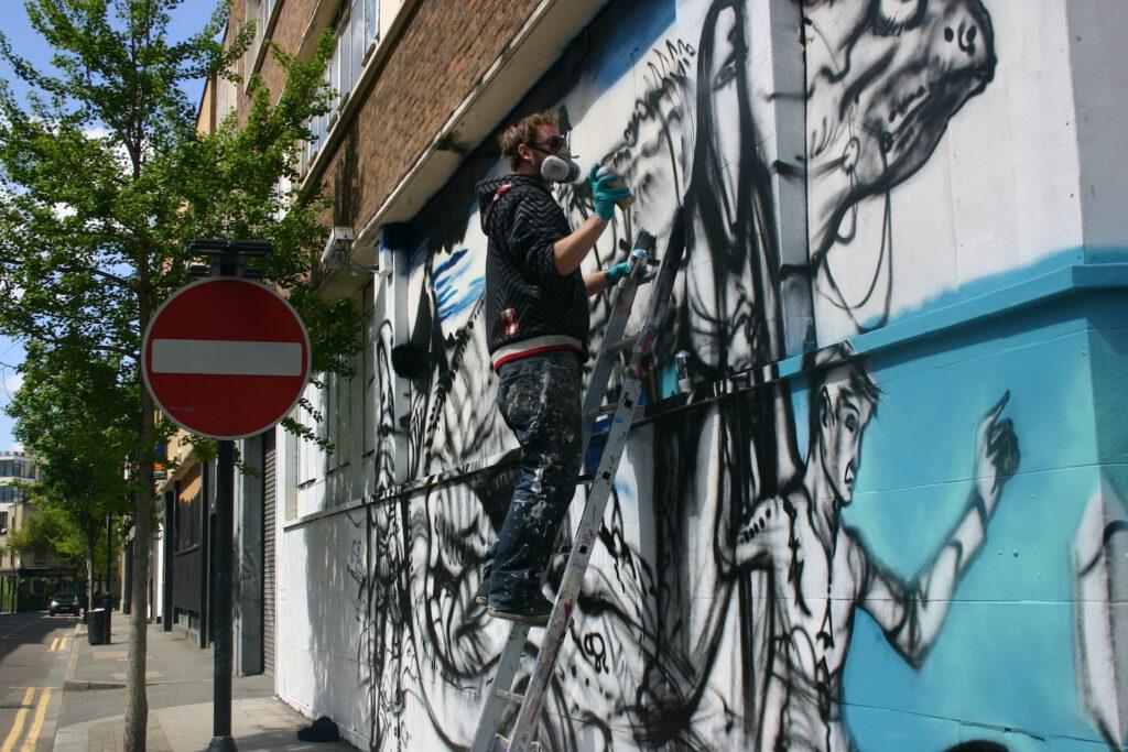 London: Probs, der Steetartist balanciert auf seinem wackeligen Gerüst und sprayt was seine