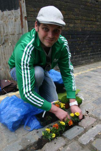 Steve Wheen im Osten Londons, nimmt einen Haufen Blumenerde und füllt damit einen breiten Spalt im Kopfsteinpflaster einer Seitengasse der Voss Street auf.