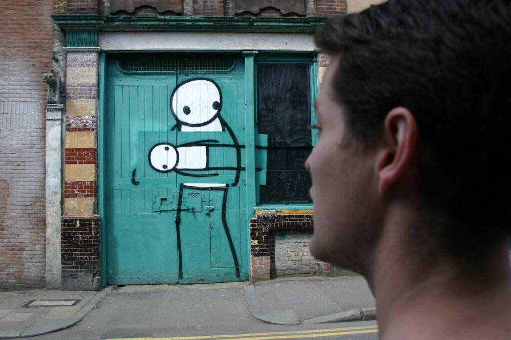 Streetart-Tourist betrachtet Kunstdiebe von Stik in Hackney